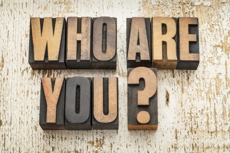 who are you question in vintage letterpress wood type on a grunge painted barn wood background Archivio Fotografico