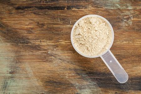 maca root: measuring scoop of maca root  powder - top view against painted wood background