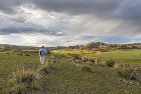 red mountain open space: male hiker with a backpack contemplates sunset over Red Mountain Open Space near Fort Collins, spring scenery Stock Photo