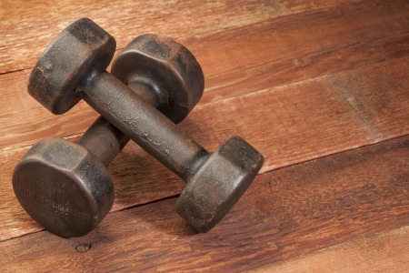 a pair of vintage iron rusty dumbbells on red barn wood background - fitness concept photo