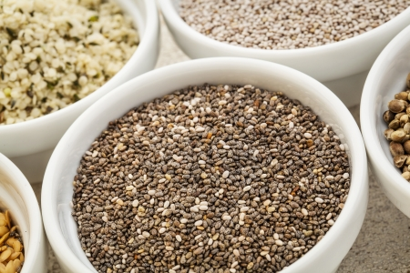hispanica: chia seeds in a white ceramic bowl among other healthy seeds Stock Photo
