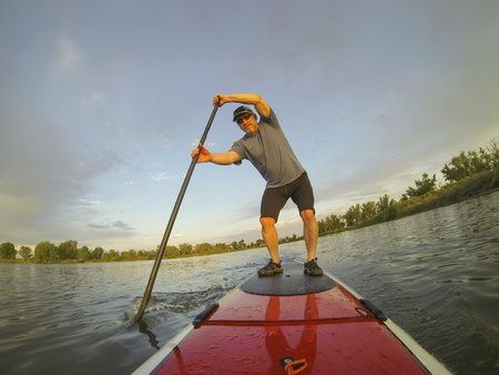 paddler: mature male paddler enjoying workout on stand up paddleboard (SUP), calm lake in Colorado, summer