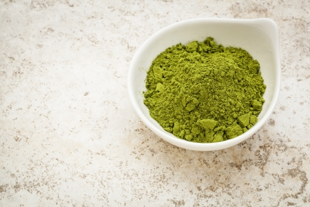 moringa leaf powder in a small bowl against a ceramic tile background Stock Photo