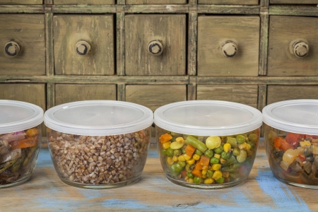 dinner leftovers (buckwheat kasha, vegetables, stir fry)  in glass  containers with drawer cabinet in background Stock Photo - 20832411