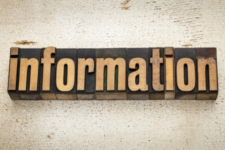 information word in vintage letterpress wood type on a grunge painted barn wood background photo