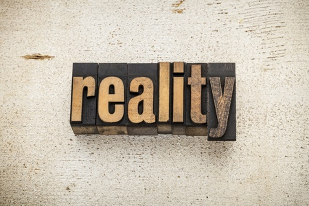 reality word in vintage letterpress wood type on a grunge painted barn wood background Stock Photo - 20832419
