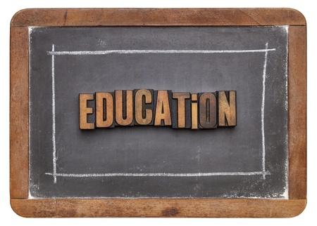 education word in vintage letterpress wood type against old slate blackboard Stock Photo - 20832421