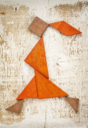 abstract figure of a walking or running girl built from seven tangram wooden pieces, a traditional Chinese puzzle game; rough white painted barn wood background Stock Photo - 20832441