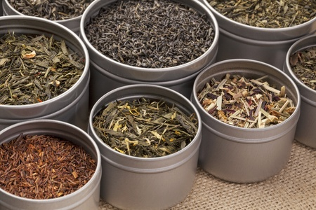 rooibos tea: samples of loose leaf green, red, black and herbal tea in metal cans on canvas background
