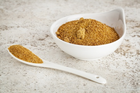 unrefined: small ceramic bowl of unrefined coconut palm sugar against a ceramic tile background with a spoon