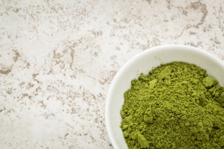 moringa: moringa leaf powder in a small bowl against a ceramic tile background with a copy space