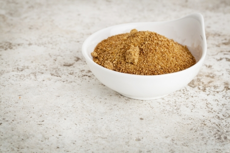 unrefined: small ceramic bowl of unrefined coconut palm sugar against a ceramic tile background with a copy space