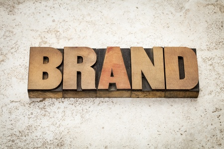 brand word in vintage letterpress wood type on a ceramic tile background photo