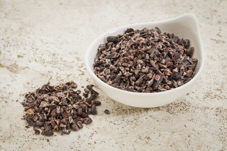 small ceramic bowl of  raw cacao nibs  against a ceramic tile background with a copy space