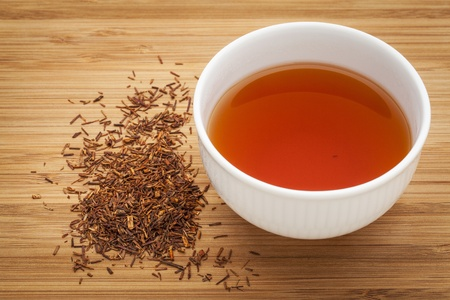 caffeine free: rooibos red tea  -  a white cup of a drink and loose leaves on bamboo wood background, tea made from the South African red bush, naturally caffeine free