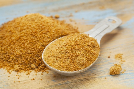 sugar palm: unrefiined coconut palm sugar - measuring tablespoon and pile on wood surface