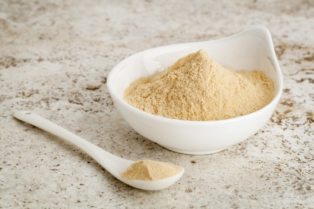 maca root powder - a small bowl with a spoon against ceramic tile surface Stock Photo