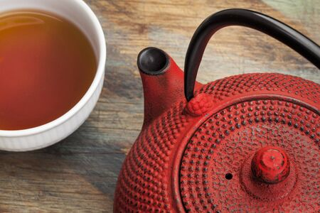 tetsubin: red tetsubin with a cup of tea - a detail of a traditional cast iron Japenese teapot