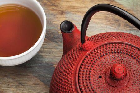 japenese: tetsubin rojo con una taza de t? - un detalle de un reparto tradicional tetera de hierro Japenese