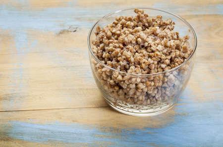 kasha: glass bowl of cooked buckwheat kasha on wood background