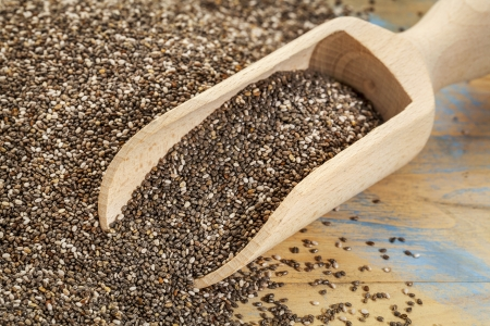 background and scoop of chia seeds on wooden surface Stock Photo - 21642231