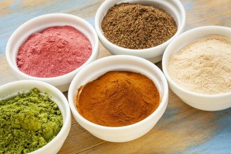 moringa: super fruit and leaf powders in small ceramic bowls - baobab, nori, yumberry, moringa, mangosteen