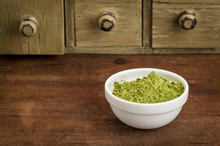 oleifera: moringa leaf powder in a small bowl with a rustic drawer cabinet