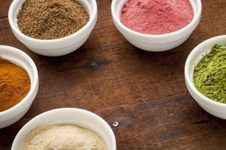 pink brown: super fruit and leaf powders in small ceramic bowls with copy space - baobab, nori, yumberry, moringa, mangosteen Stock Photo