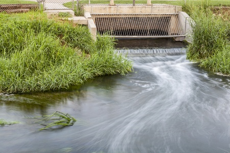 treatment plant: Processed and cleaned sewage flowing out from water reclamation facility to a river