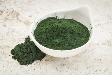 algaes: small bowl of Hawaiian spirulina powder against a ceramic tile  background