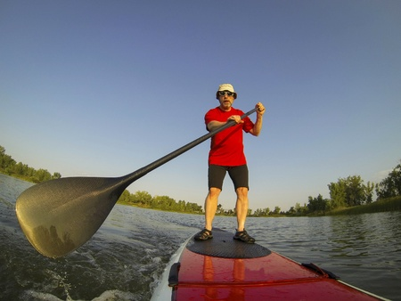 mature male paddler enjoying workout on stand up paddleboard  SUP , calm lake in Colorado, summer, distorted wide angle view