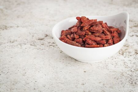 small ceramic bowl of  dried goji berries against a ceramic tile background with a copy space photo