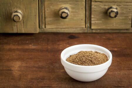 morinda: noni fruit powder  from Hawaiian evergreen shrub in a small bowl with a rustic drawer cabinet