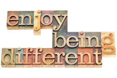 enjoy being different advice - lifestyle or nonconformist concept - isolated text in letterpress wood type