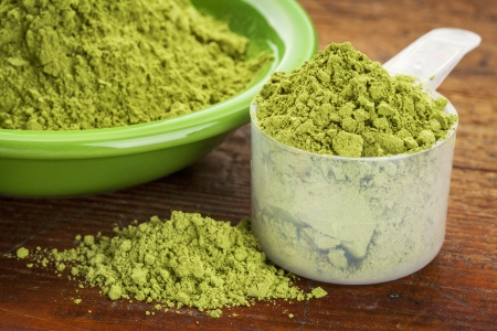 moringa: measuring scoop of moringa leaf powder with a bowl on wooden surface Stock Photo