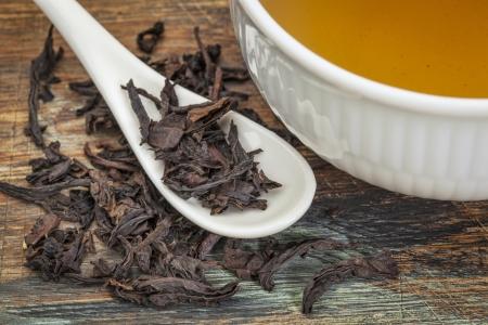 loose leaf: una taza de t� oolong negro con hojas sueltas y cucharita