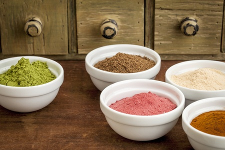 super bowl: super fruit and leaf powders in small ceramic bowls - baobab, noni, yumberry, moringa, mangosteen Stock Photo