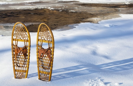 classic wooden Bear Paw snowshoes on the shore of partially frozen Cache la Poudre River near Fort Collins, Colorado Stock Photo - 21921191