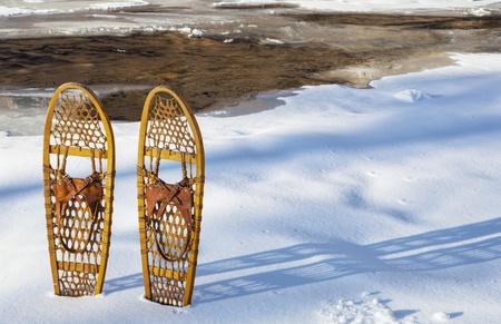 Raquetas de madera cl?sicos Bear Paw en la orilla del parcialmente congelado Cache la Poudre River, cerca de Fort Collins, Colorado Foto de archivo - 21921191