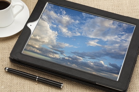 cloud computing concept - a stormy cloudscape on digital tablet computer together with a cup of coffee and stylus pen photo