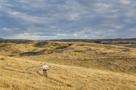 a lonely male biking over rolling prairie illuminated by sunrise at Soapston Prairie Natural Area in northern Colorado near Fort Collins, late summer
