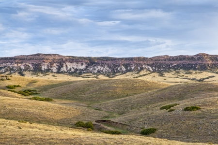 rolling prairie and cliff illuminated by sunrise at Soapstone Prairie Natural Area in northern Colorado near Fort Collins, late summer Stock Photo - 22435801