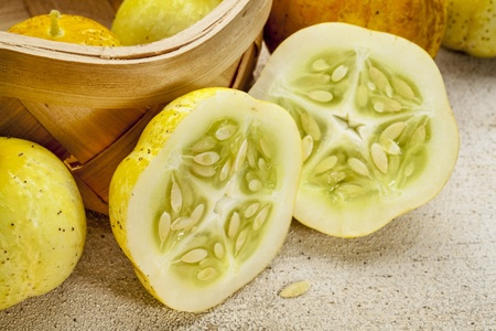 lemon (or apple) cucumbers in a basket and on rough white painted wood surface Stock Photo - 22443333