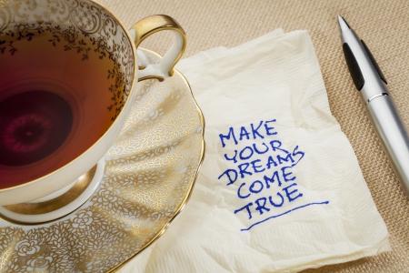 maak je dromen waar - motiverende slogan op een servet met een kopje thee