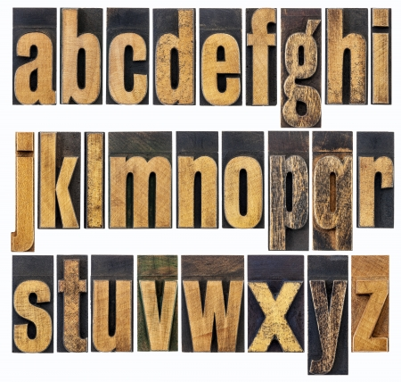 complete English lowercase alphabet - a collage of 26 isolated antique wood letterpress printing blocks, scratched and stained by inks Stock Photo