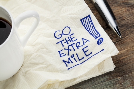 mile: go the extra mile - motivational slogan on a napkin with a cup of coffee