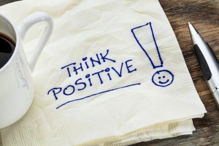 actitud positiva: pensar en positivo - lema motivacional en una servilleta con una taza de café