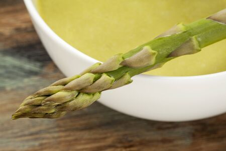 a bowl of asparagus cream soup with green asparagus spear Stock Photo - 22443410