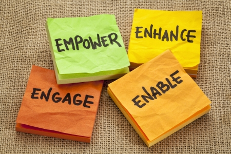 enhance: empower, enhance, enable and engage - business motivation concept -  handwriting on sticky notes