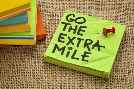 mile: go the extra mile  - motivational reminder or procrastination concept  - handwriting on sticky note - handwriting on sticky note